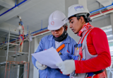two men in hard hats look at a white paper together