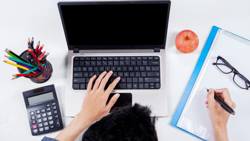 Person working on a table with laptop, papers, calculator, pens, apple and glasses